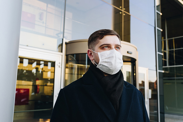 A man wearing a face mask in front of a building