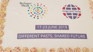 A cake featuring Migrant Help and Refugee Week logos