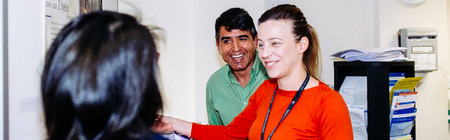 Migrant Help adviser talking to clients in an office