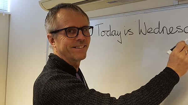 A man writing in a whiteboard reading Today is Wednesday