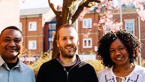 Three Migrant Help staff smiling in front of a blossom tree on a sunny day.
